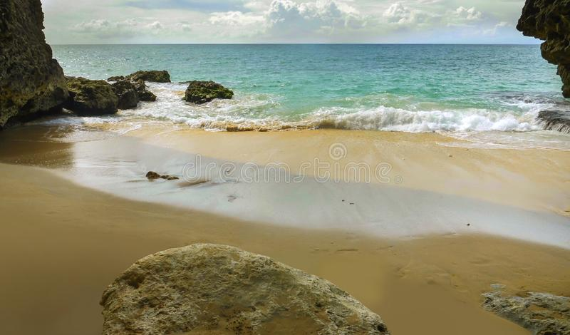 Beautiful scenic view from rock cave of Asian tropical desert beach paradise in Indonesia with stunning vivid sea water color in. Summer holidays travel and stock images