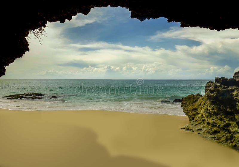 Beautiful scenic view from rock cave of Asian tropical desert beach paradise in Indonesia with stunning vivid sea water color in. Summer holidays travel and royalty free stock images