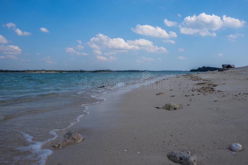 Beautiful scenic view of shoreline in Belitung, Indonesia. With calm waves under blue cloudy sky. Close up of soft sand in low angle view royalty free stock photo