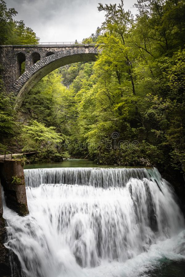 Beautiful scenic vintgar gorge with stone bridge arch above waterfall. Close up stock image
