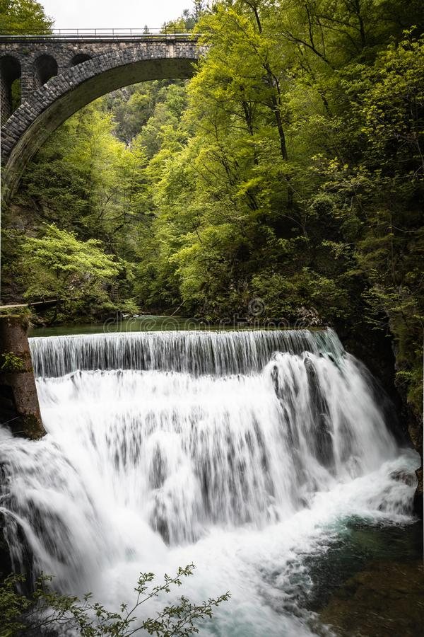 Beautiful scenic vintgar gorge with stone bridge arch above waterfall. Close up royalty free stock photo