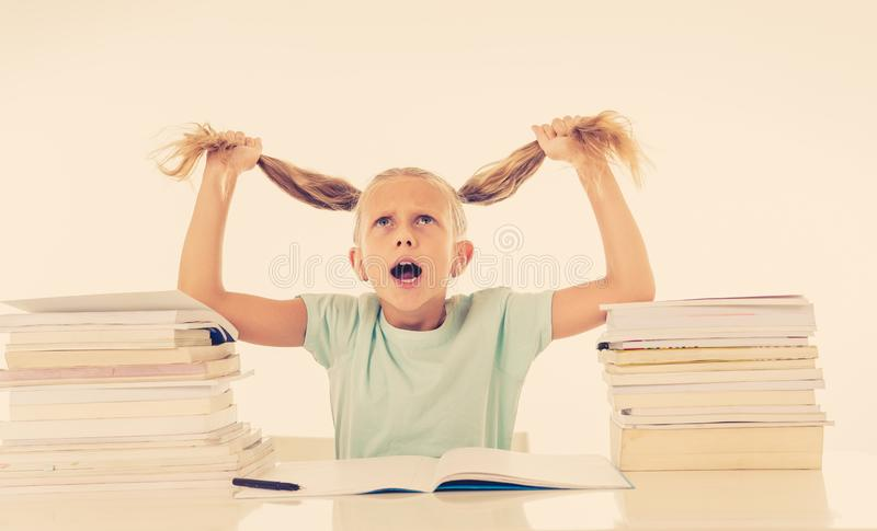 Stressed girl having too many homework in motivation low performance children. Beautiful school girl trying to study having too many homework that It is driving royalty free stock photo