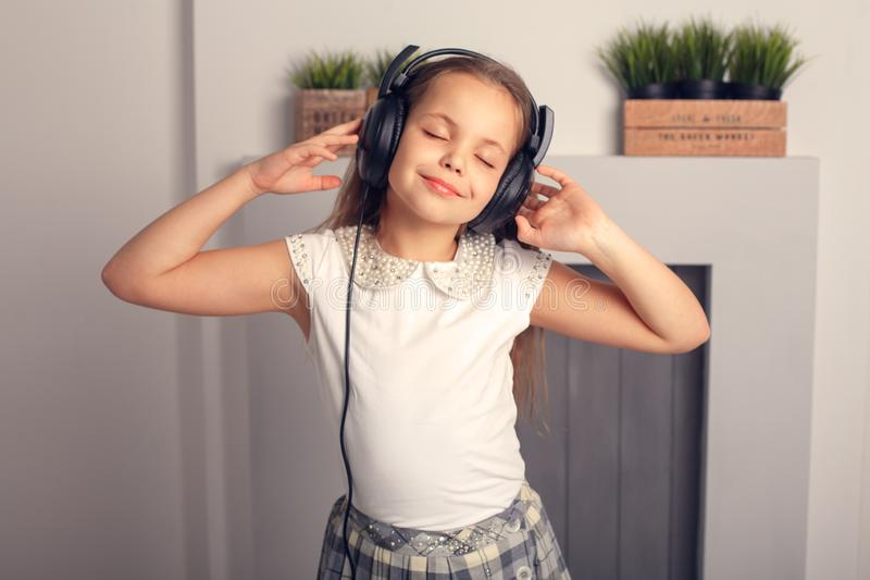 Beautiful schoolgirl listens to a song in the headphones. The co stock photo