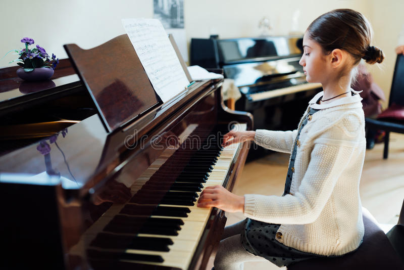 Beautiful schoolgirl playing piano at music school royalty free stock images