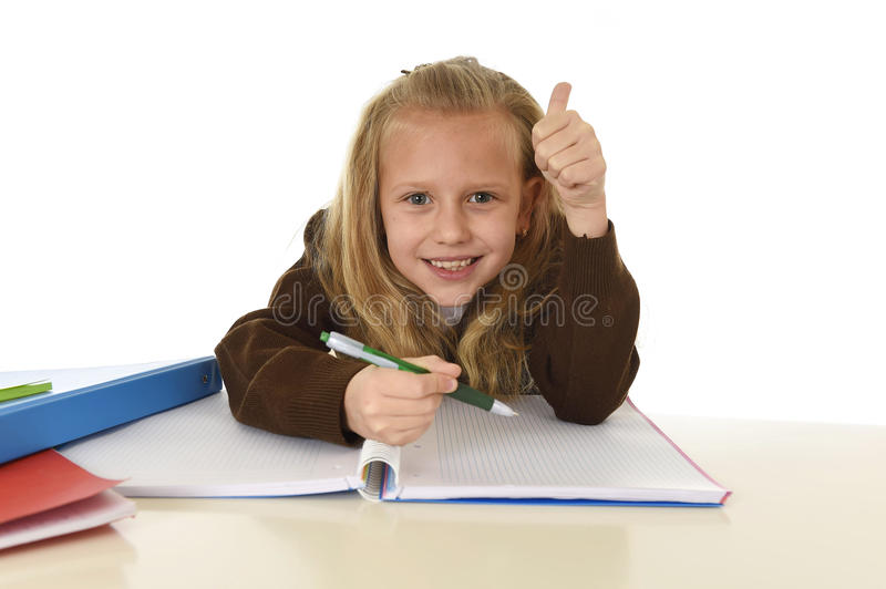 Beautiful schoolgirl in school uniform with blond hair smiling happy sitting on desk doing homework. Little beautiful schoolgirl in school uniform with blond royalty free stock images