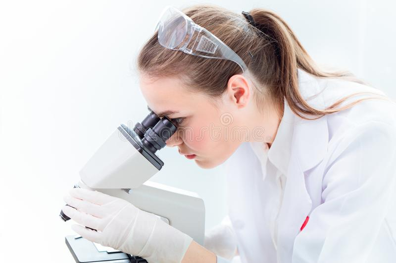 Beautiful scientist working on microscope in medical lab stock images