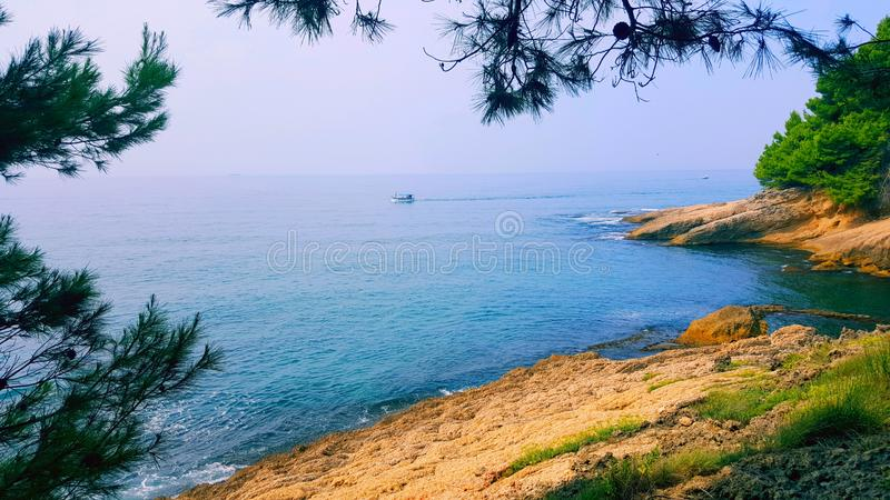 The beautiful sea coast and beautiful blue water is the right place to rest and enjoy. Small ship in the background. The beautiful sea coast and beautiful blue stock photos