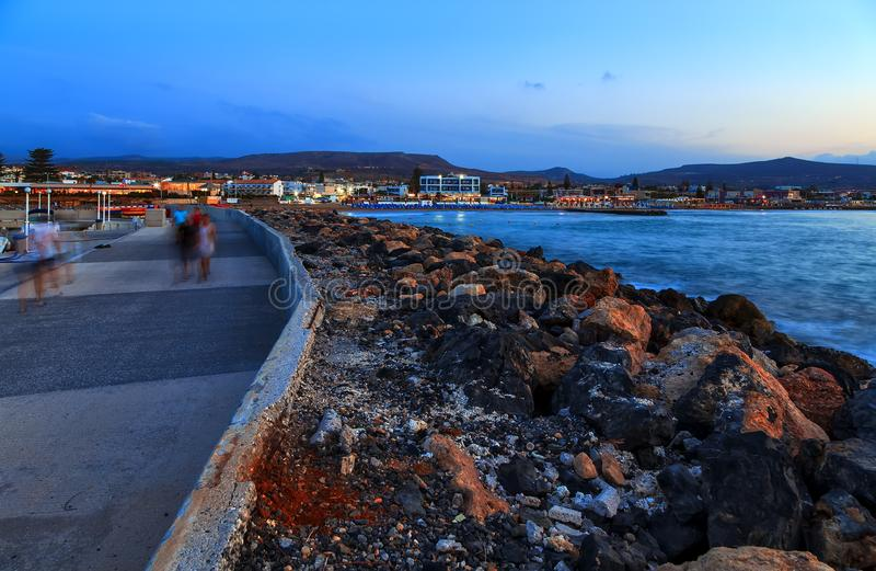 Beautiful sea with evening soft light of the sunset against cloudy sky with coastal line with stones and promenade path royalty free stock images
