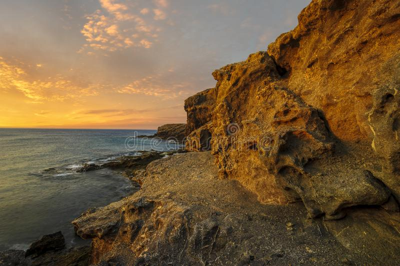 Beautiful sea landscape - sunset over a rocky ocean cliff.Punta Papagayo royalty free stock images