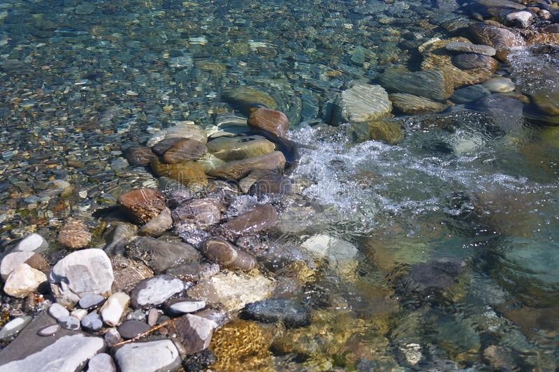 Beautiful sea pebbles under the flowing water on beach royalty free stock images