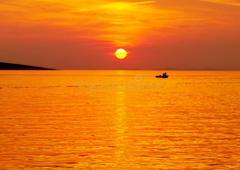 Beautiful sea sunset in yellow and orange color tone with small fishing boat royalty free stock photo