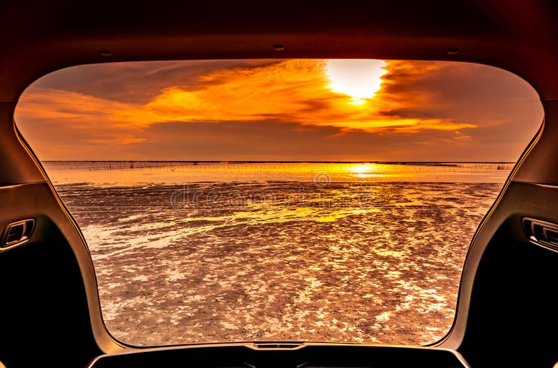 Beautiful sea view from inside car trunk. Sea view with orange sky and clouds in sunset time at the beach. Freedom summer travel royalty free stock photography