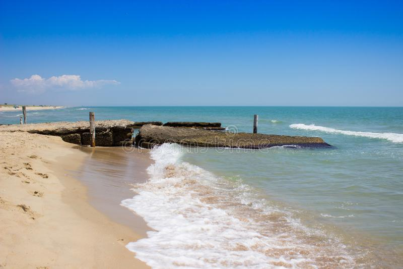 A beautiful sea view, a sandy beach and an old broken breakwater. stock image