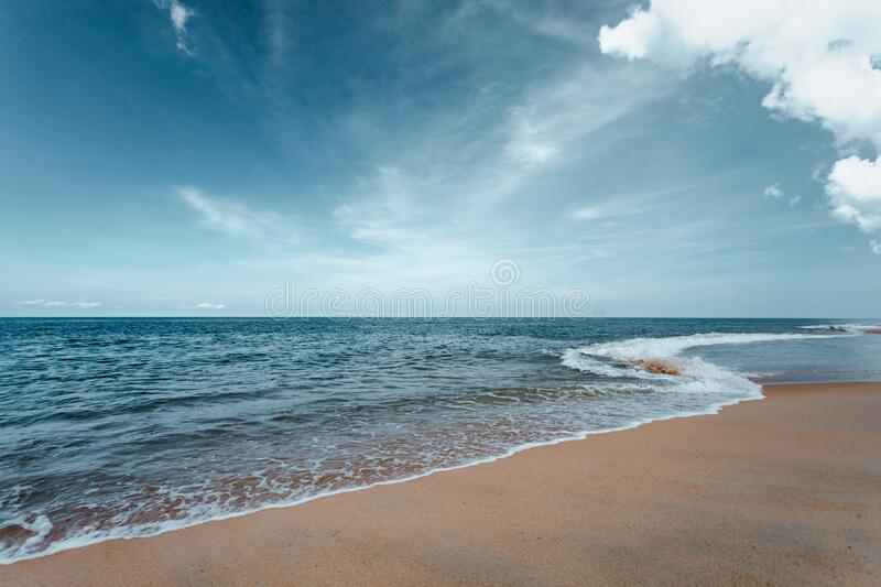 Beautiful sea waves with foam of turquoise color. Horizon with blue sky and Beautiful sand stock photos