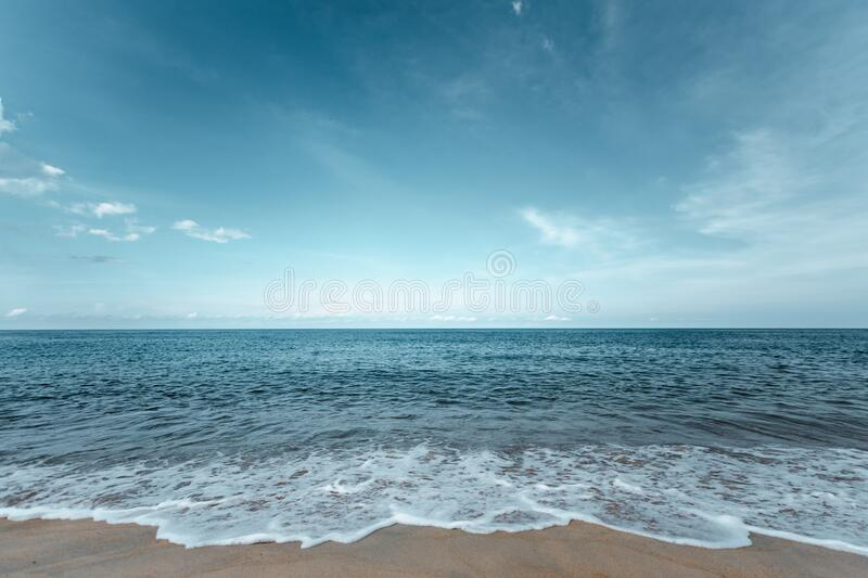 Beautiful sea waves with foam of turquoise color. Horizon with blue sky and Beautiful sand stock images