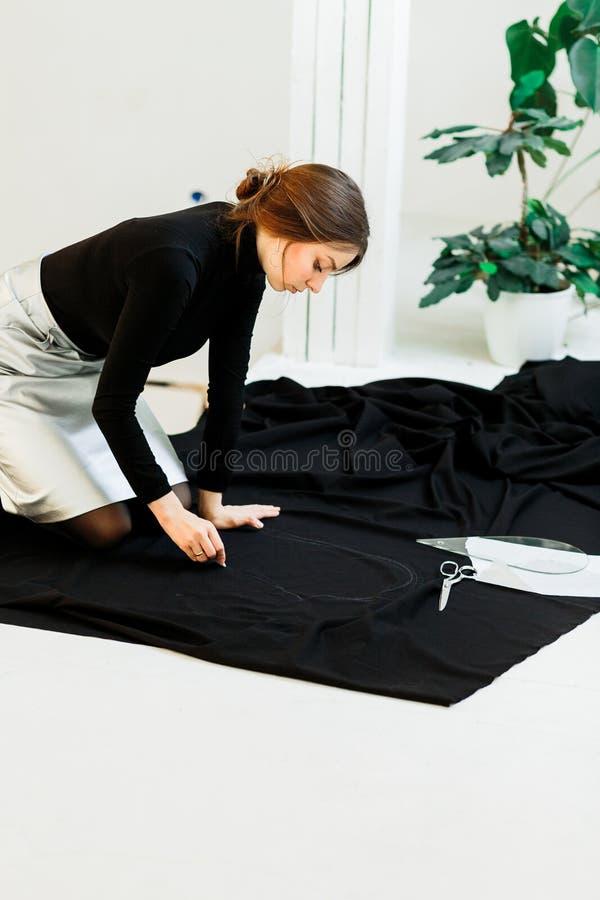 Beautiful seamstress, cut black fabric on the studio floor royalty free stock images