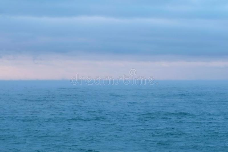 Beautiful seascape with pink sunset and blue clouds. Calm sea. royalty free stock images