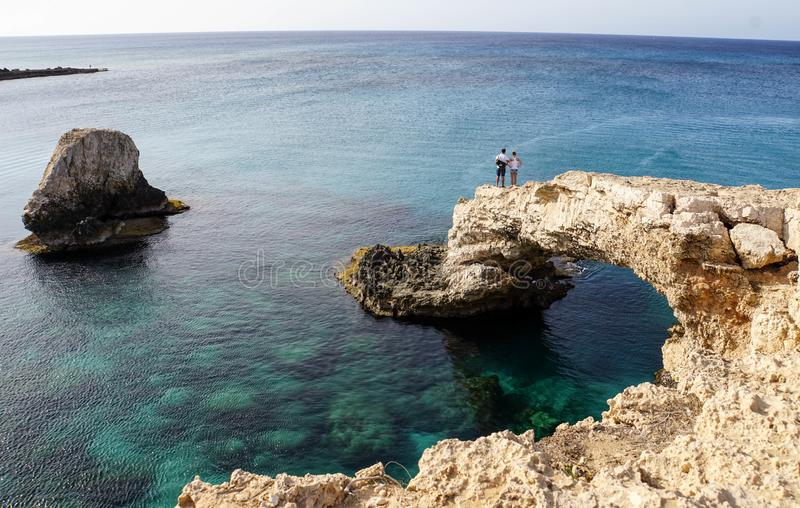 beautiful seascape. Rocky shore. Rocky shore. Arch in the rock. Lovers on the rock admire the sea. Azure sea stock photos
