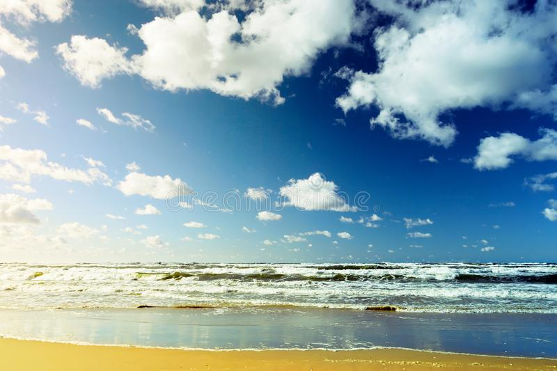 Beautiful seascape with sea waves, blue sky, white cumulus clouds and sand beach. Summer vacation tropical landscape. stock photos