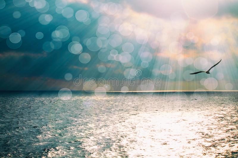 Beautiful seascape with shiny reflection on ocean blue water and sun rays. stock photo