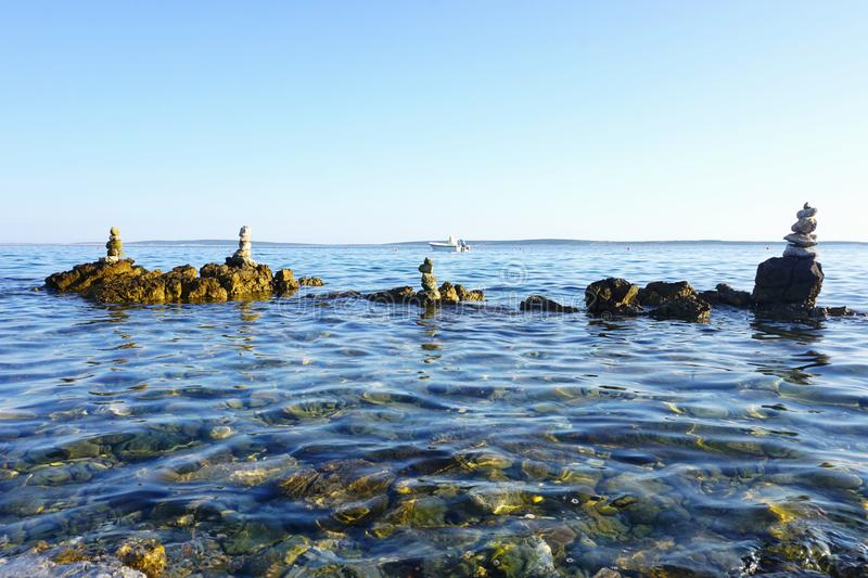 Beautiful seascape with stacked stones in the water royalty free stock image