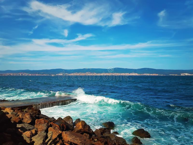 Wavy blue sea. Beautiful seashore landscape as the wavy blue sea and stone beach with a hills on the horizon. Nessebar, Bulgaria stock images