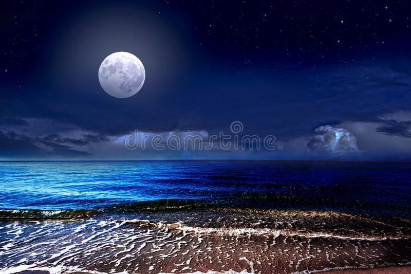 Full moon over the sea and starry sky stock image