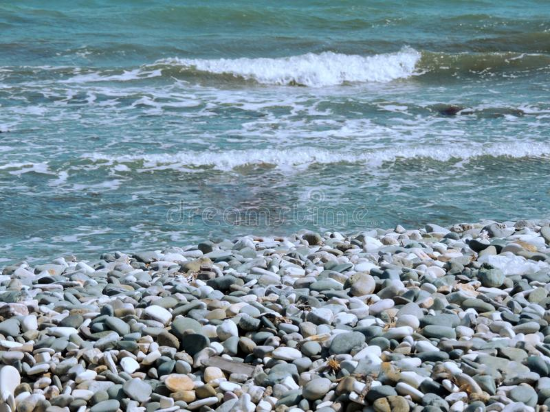 Beautiful seashore with waves and colored stones stock images