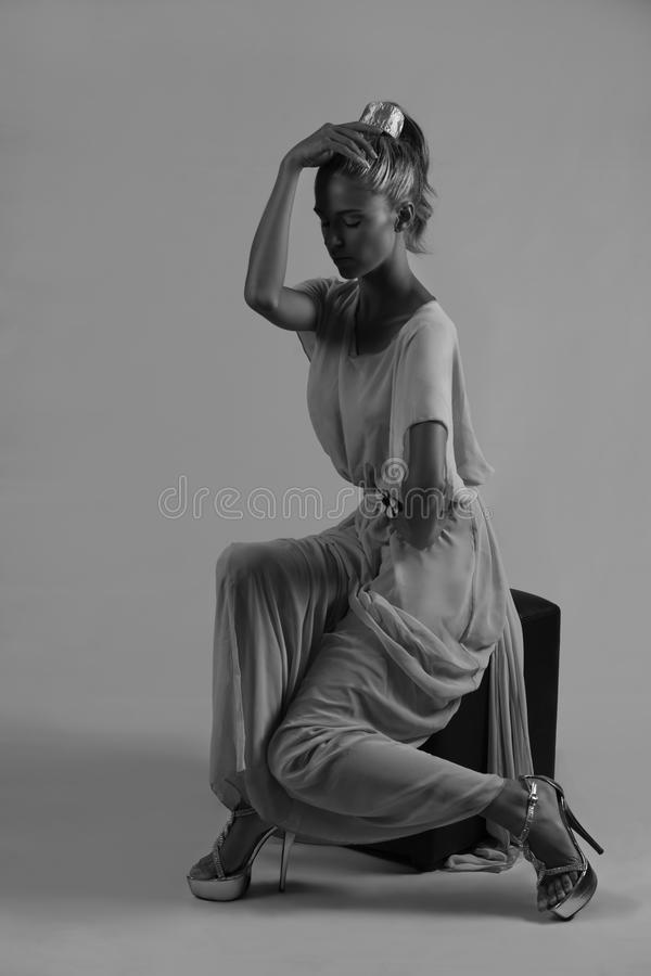 Beautiful seated woman in monochrome. Portrait of a beautiful young Caucasian woman wearing her blonde hair in a high ponytail with hairband, posing with her royalty free stock photo