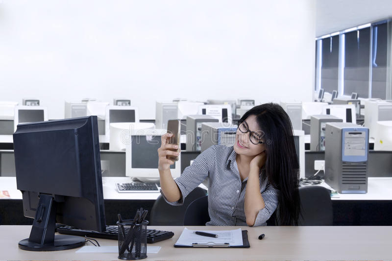 Beautiful secretary makes selfie photo in the office stock images