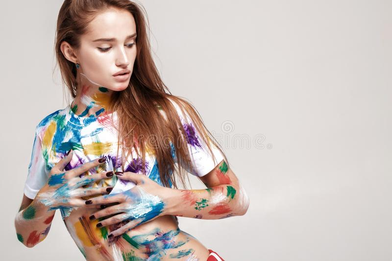 Young woman smeared in multicolored paint. royalty free stock image