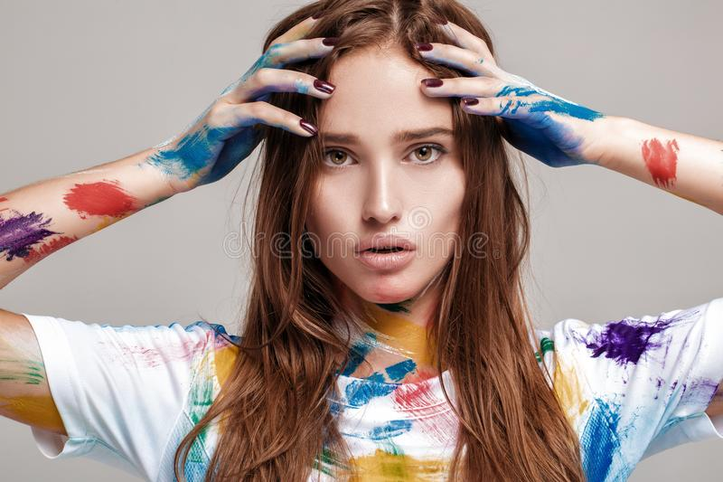 Young woman smeared in multicolored paint. stock photos