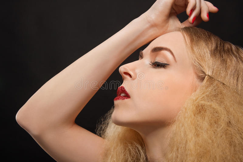 Beautiful seductive woman with parted lips. Beautiful seductive blond woman with red parted lips and a sultry expression looking sideways at the camera with an royalty free stock photography