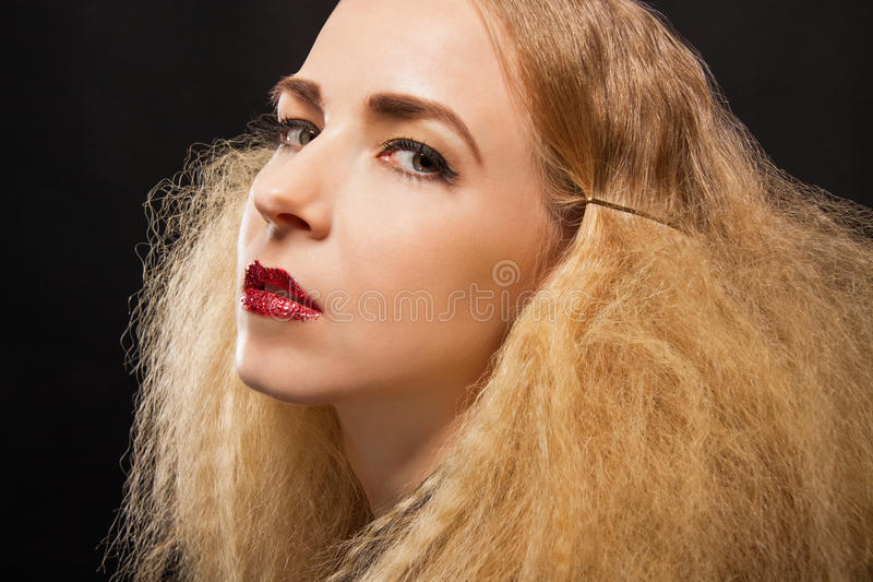 Beautiful seductive woman with parted lips. Beautiful seductive blond woman with red parted lips and a sultry expression looking sideways at the camera with an royalty free stock images