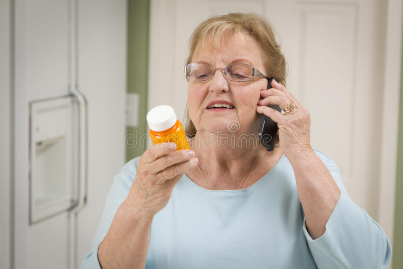 Senior Adult Woman on Cell Phone Holding Prescription Bottle royalty free stock photography