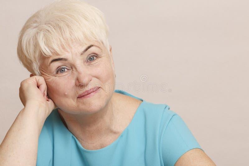 Beautiful senior blond woman in blue dress. stock photo
