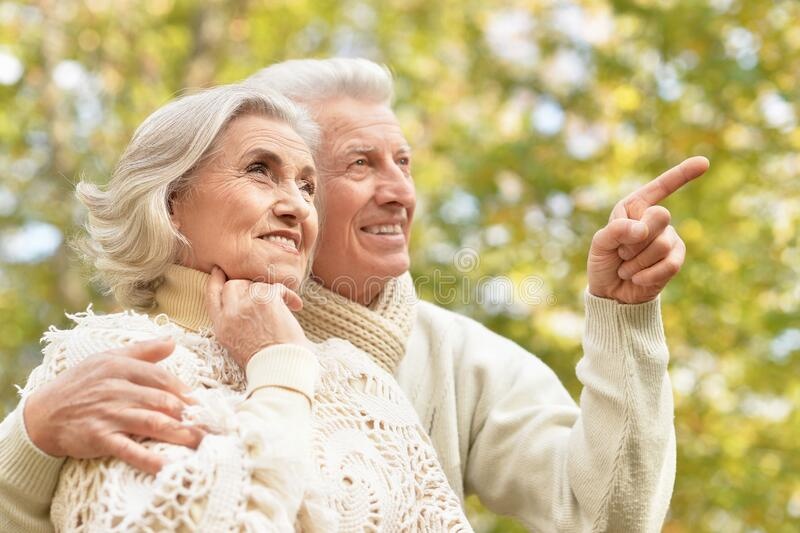 Beautiful senior couple in the park. Man pointing with finger royalty free stock images
