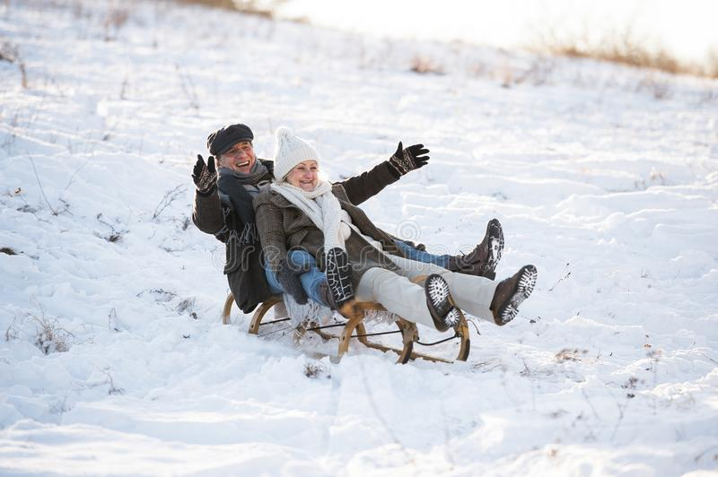 Beautiful senior couple on sledge having fun, winter day. Beautiful senior women and men on sledge having fun in sunny winter nature royalty free stock photography