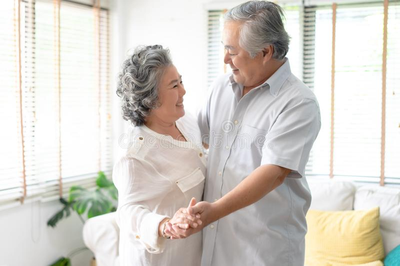 Beautiful senior couple smiling in love dancing at home.Happy li stock photos
