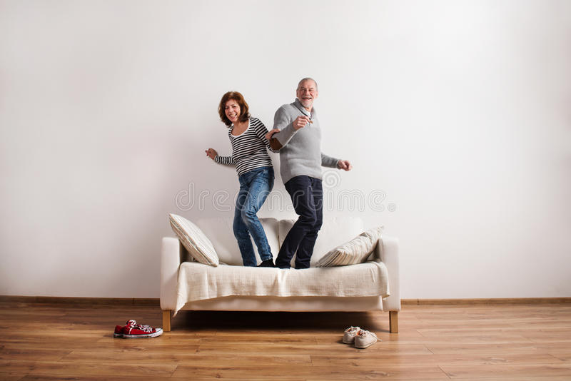 Beautiful senior couple standing on couch, dancing. Studio shot. Beautiful senior couple in love standing on couch, dancing, having fun. Studio shot against stock image