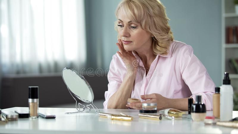 Beautiful senior female applying foundation in front of mirror home, skin care. Stock photo royalty free stock photos