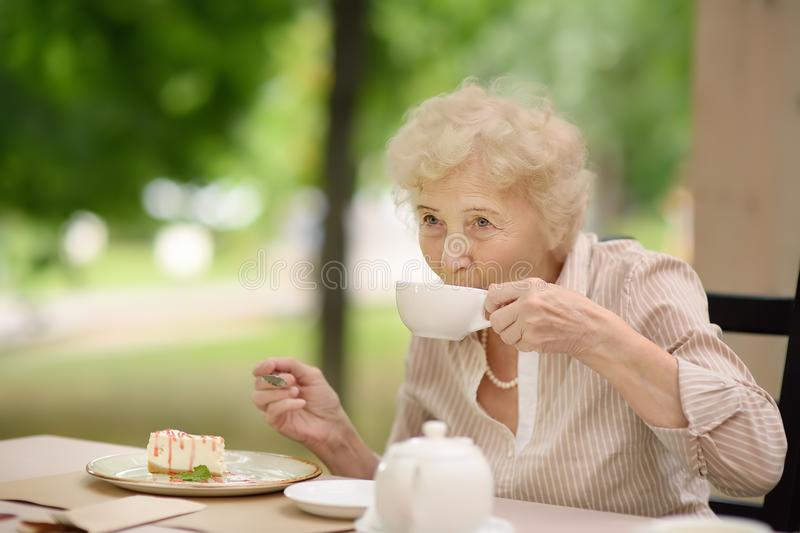 Beautiful senior lady with curly white hair drinking tea in outdoors cafe or restaurant stock image