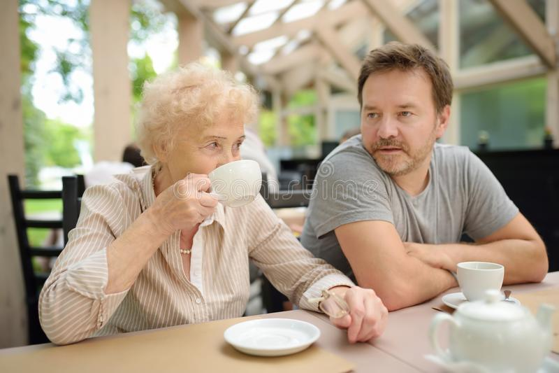 Beautiful senior lady with his mature son drinking tea in outdoors cafe or restaurant. Elderly lady lifestyle stock image