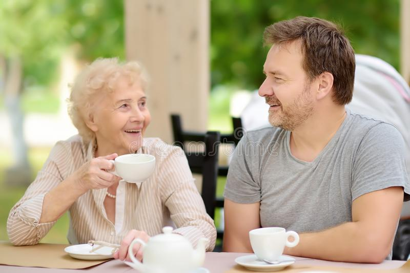 Beautiful senior lady with his mature son drinking tea in outdoors cafe or restaurant. Elderly lady lifestyle stock images