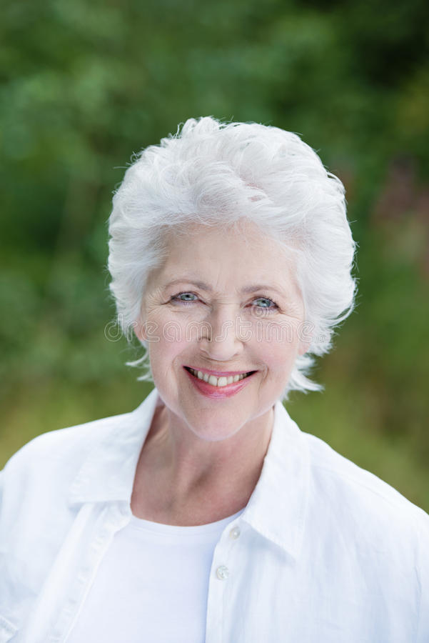Beautiful senior lady outdoors in the park stock images