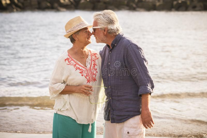 Beautiful senior mature couple enjoy with kiss and hug the outdoor leisure activity at the beach during vacation or new retirement royalty free stock photo