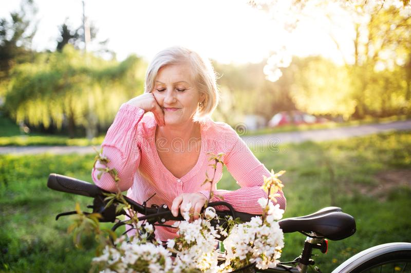 Beautiful senior woman with bicycle outside in spring nature. stock photography