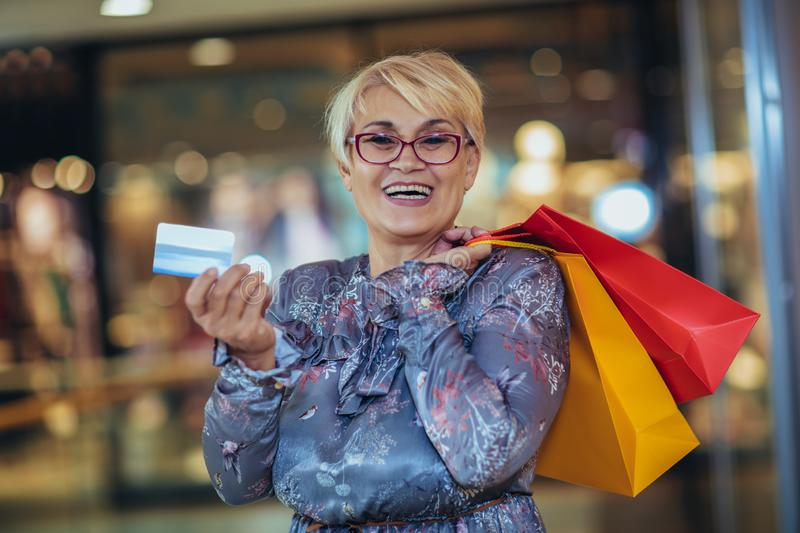 Beautiful senior woman holding credit card royalty free stock photography
