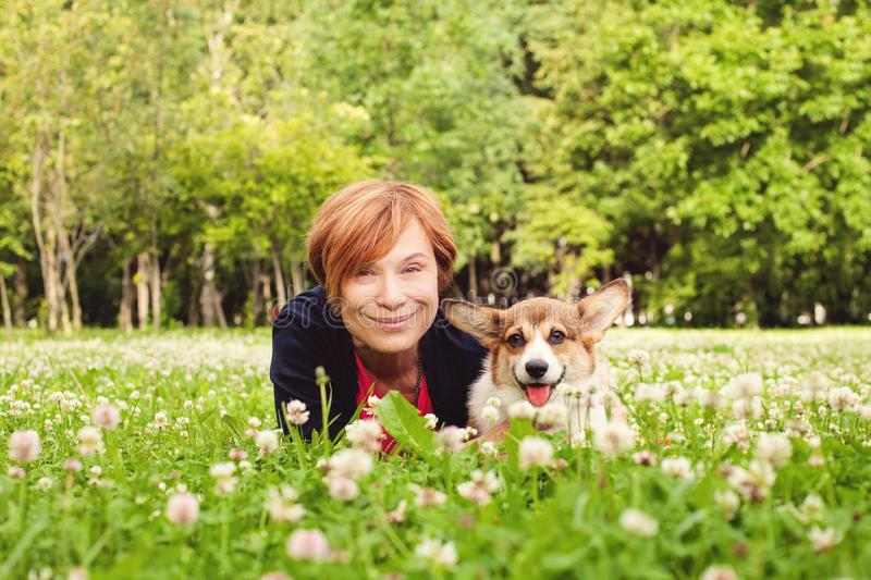 Beautiful senior woman with dog in spring nature royalty free stock image