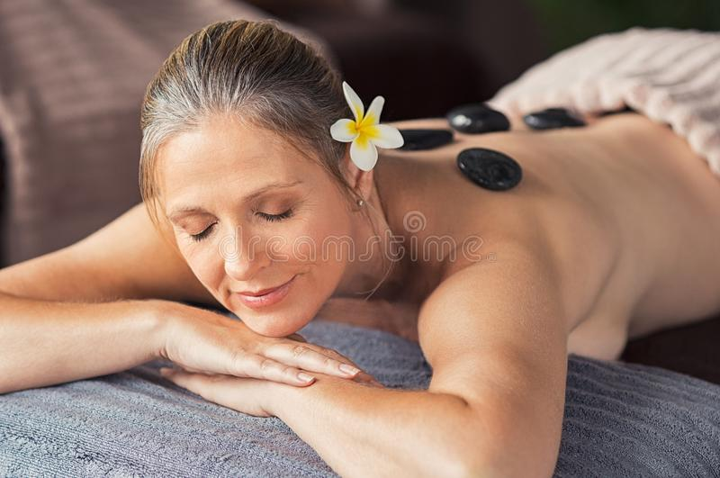 Relaxed woman with hot stones on back stock images